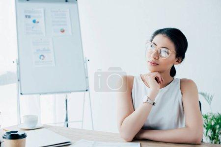 Photo pour Femme d'affaires latine rêveuse dans des lunettes regardant loin tout en étant assis sur le lieu de travail - image libre de droit