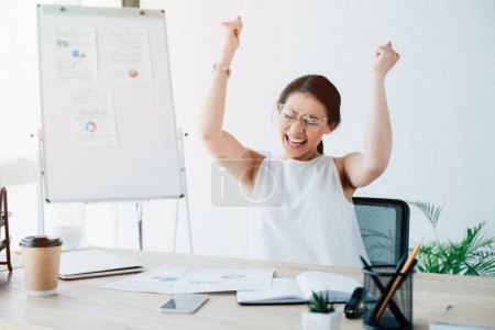Photo for Excited businesswoman celebrating triumph while sitting at workplace in office - Royalty Free Image