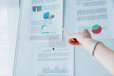 Photo for Cropped shot of businesswoman pointing at flipchart with infographics - Royalty Free Image