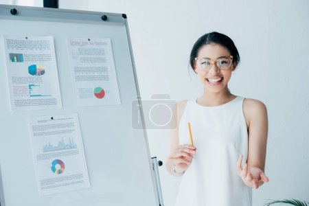 Photo for Cheerful businesswoman gesturing while standing near flipchart with infographics and looking at camera - Royalty Free Image