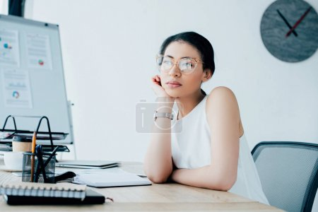 dreamy businesswoman in glasses looking away while sitting at workplace in office