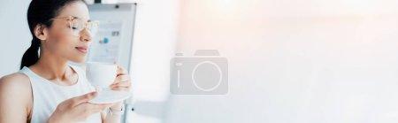 Photo pour Tir panoramique de belle femme d'affaires tout en retenant la tasse de café avec les yeux fermés - image libre de droit