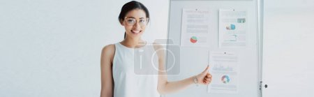 Photo for Panoramic shot of cheerful latin businesswoman showing thumb up while standing near flipchart with infographics - Royalty Free Image