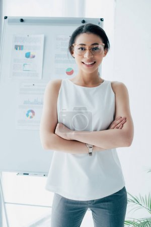 Photo for Pretty latin businesswoman in glasses smiling at camera while standing with crossed arms in office - Royalty Free Image