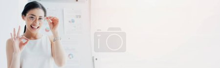 Photo for Panoramic shot of cheerful latin businesswoman touching glasses and showing okay gesture at camera - Royalty Free Image