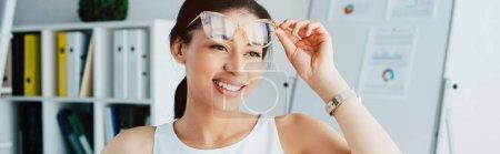 Photo pour Tir panoramique de la femme d'affaires latine gaie touchant des verres et regardant loin dans le bureau - image libre de droit