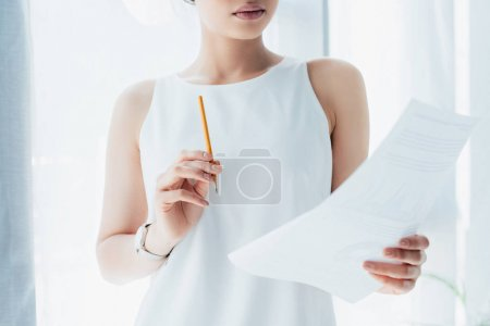 Photo for Cropped shot of young latin businesswoman looking at document and holding pencil - Royalty Free Image
