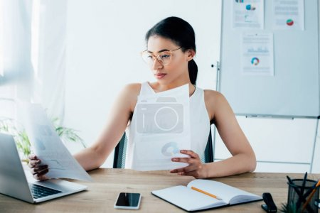 Photo for Attentive latin businesswoman doing paperwork while sitting at desk in office - Royalty Free Image