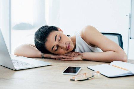 Photo pour Femme d'affaires latine épuisée dormant au lieu de travail près du cahier et du smartphone avec l'écran blanc - image libre de droit