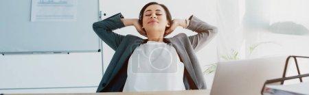 Photo pour Tir panoramique de femme d'affaires latine fatiguée détendant avec des mains au-dessus de la tête dans le bureau - image libre de droit