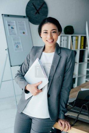 schöne lateinische Geschäftsfrau lächelt in die Kamera, während sie Papiermappe in der Hand hält