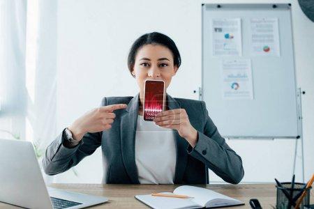 Photo pour Jolie femme d'affaires latine pointant du doigt avec smartphone avec trading cours app à l'écran - image libre de droit
