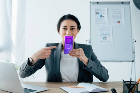 Photo pour Young latin businesswoman pointing with finger at smartphone with shopping app on screen - image libre de droit