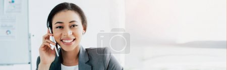 Photo for Panoramic shot of cheerful latin businesswoman talking on smartphone and smiling at camera - Royalty Free Image