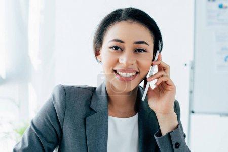 Photo pour Belle femme d'affaires latine souriant à l'appareil-photo tout en parlant sur le smartphone dans le bureau - image libre de droit