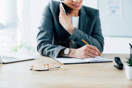 Photo pour Plan recadré de souriantes femmes d'affaires latines écrivant dans un carnet tout en parlant sur smartphone - image libre de droit