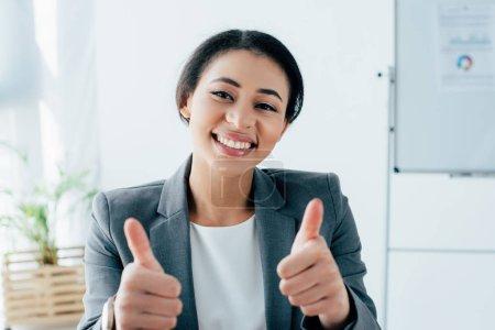 Foto de Alegre mujer de negocios latina mostrando los pulgares hacia arriba mientras sonríe a la cámara - Imagen libre de derechos