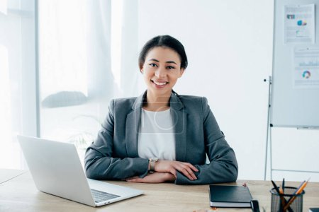 Photo pour Attractive latin businesswoman sitting at workplace near laptop and smiling at camera - image libre de droit