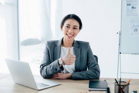 Photo for Beautiful latin businesswoman showing thumb up while sitting at workplace near laptop and smiling at camera - Royalty Free Image
