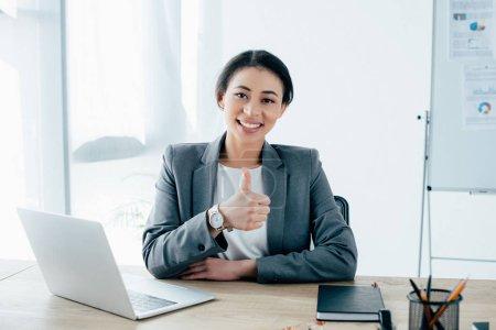 Photo pour Belle femme d'affaires latine montrant pouce vers le haut tout en étant assis sur le lieu de travail près d'un ordinateur portable et souriant à la caméra - image libre de droit