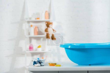 Photo pour Baignoire bébé bleue près de baskets bébé et jouets dans la salle de bain - image libre de droit