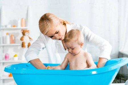 Photo pour Blonde femme regardant mignon tout-petit fils prenant bain - image libre de droit