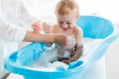 cropped view of mother washing smiling toddler kid in blue baby bathtub