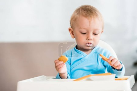 Photo for Cute toddler kid sitting in feeding chair near sweet cookies at home - Royalty Free Image