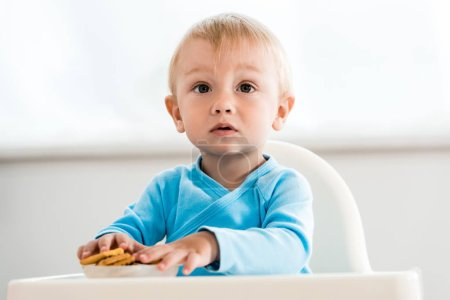 Photo for Cute toddler child sitting in feeding chair near tasty cookies at home - Royalty Free Image