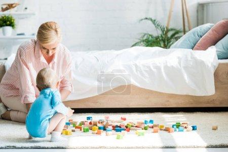 Foto de Atractiva madre rubia sentada cerca de niño pequeño hijo y bloques de juguete en el dormitorio - Imagen libre de derechos