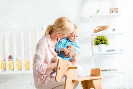 Photo for Blonde mother holding in arms cute toddler son near rocking horse - Royalty Free Image