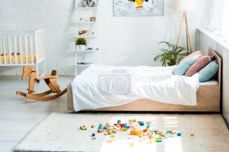 Photo pour Cheval à bascule en bois près du lit avec literie blanche et blocs jouets sur tapis - image libre de droit