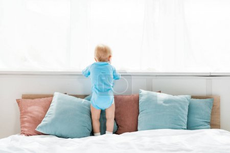 Photo for Back view of toddler kid standing on bed and looking at window in bedroom - Royalty Free Image