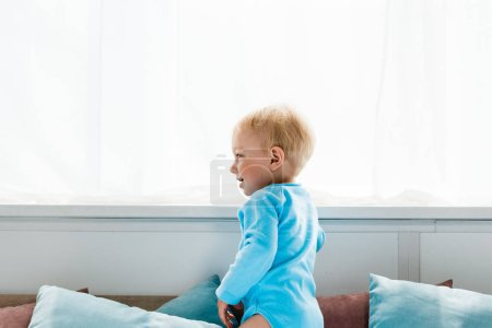 Photo for Cheerful toddler kid standing and smiling in bedroom - Royalty Free Image
