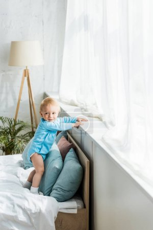 Photo for Cute and smiling kid standing on bed in modern bedroom - Royalty Free Image