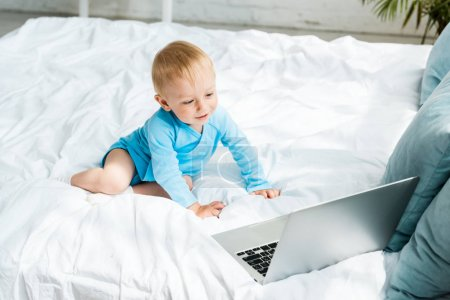 happy toddler kid looking at laptop while sitting on bed at home