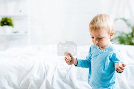 Foto de Adorable niño pequeño de pie con juguetes de madera cerca de la cama en casa - Imagen libre de derechos