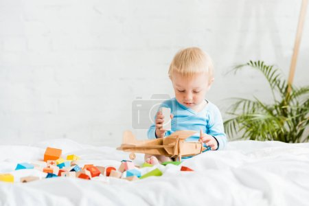 Photo for Cute toddler boy playing with wooden biplane near colorful toy blocks on bed - Royalty Free Image