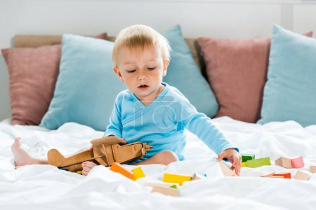 Foto de Toddler kid playing with wooden biplane near colorful toy blocks on bed - Imagen libre de derechos