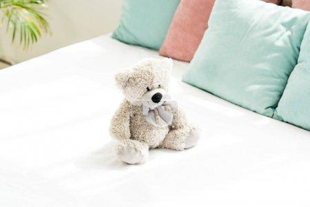 Photo pour Ours en peluche gris près des oreillers roses et bleus sur la literie blanche dans la chambre à coucher - image libre de droit