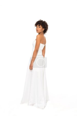 Photo for Attractive and curly african american bride standing in wedding dress isolated on white - Royalty Free Image