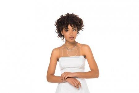 Photo pour Femme américaine africaine attirante restant dans la robe de mariage d'isolement sur le blanc - image libre de droit