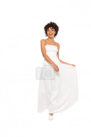 Photo for Happy african american bride smiling while touching wedding dress isolated on white - Royalty Free Image