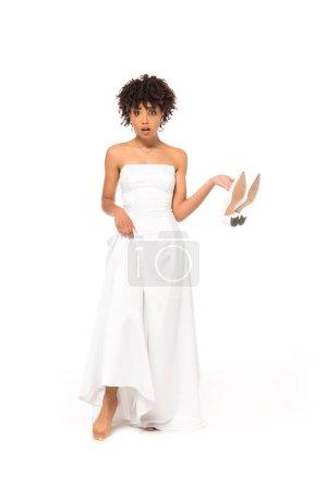 Photo pour Surprise mariée américaine africaine touchant robe de mariée et la tenue des chaussures tout en restant isolé sur le blanc - image libre de droit