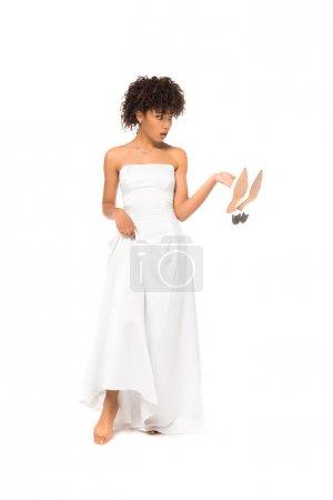 Photo pour Mariée américaine africaine touchant la robe de mariage et les chaussures de fixation tout en restant isolé sur le blanc - image libre de droit