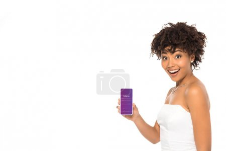 Photo for KYIV, UKRAINE - MAY 16, 2019:Happy african american bride holding smartphone with instagram app on screen isolated on white - Royalty Free Image