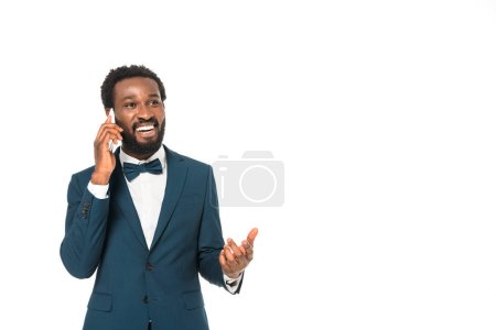 Photo for Happy african american man in suit talking on smartphone isolated on white - Royalty Free Image
