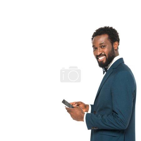 Photo pour Heureux homme afro-américain en costume tenant smartphone isolé sur blanc - image libre de droit