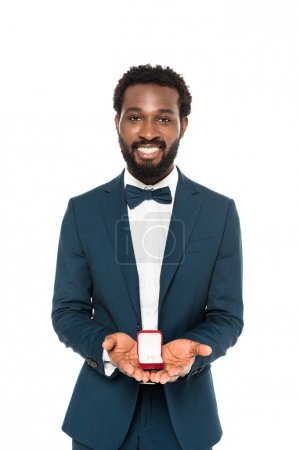 Photo for Handsome african american bridegroom holding box with wedding ring isolated on white - Royalty Free Image