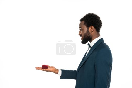 Photo for Side view of cheerful african american man holding box with wedding ring isolated on white - Royalty Free Image